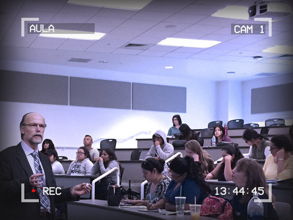 Image of a lecture hall. A professor is lecturing. Text around the outside of the image reads: Aula, Cam 1, 13:44:45. A red dot signifies recording.