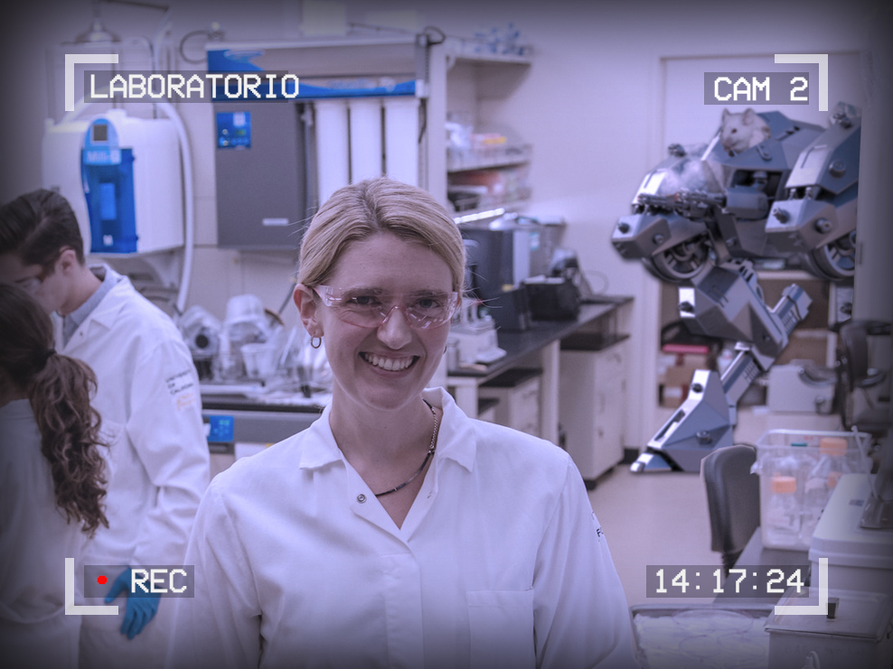 Photo of a smiling scientist in a lab. Behind her, a battle mech is coming through the doorway piloted by a white mouse. The text around the outside of the image reads: Laboratorio, Cam 2, 14:17:24, Recording