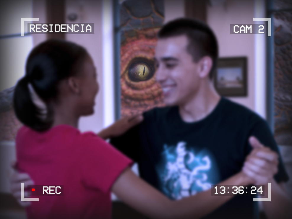 Photo of a young couple dancing. Behind them, through the window, we see the large eye of a monster or dinosaur. Text around the outside reads: Residencia, Cam 2, 13:36:24, Recording