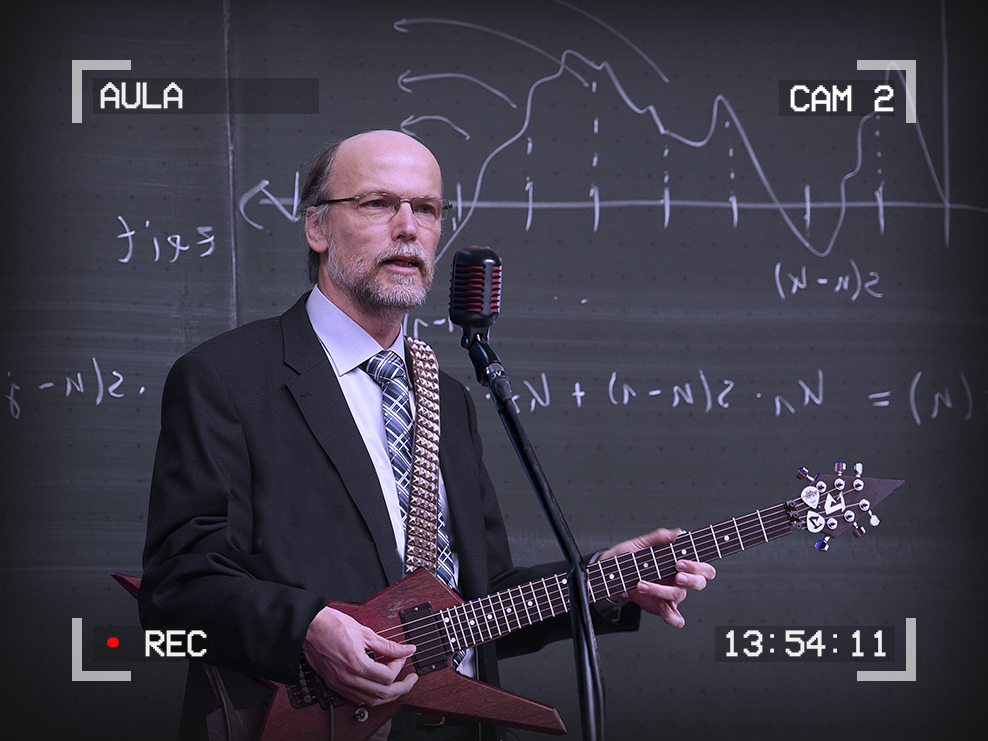 Image of a man in a suit in front of a blackboard playing electric guitar with a microphone in front of him. Text around the outside of the image reads: Aula, Cam 2, 13:54:11, Recording