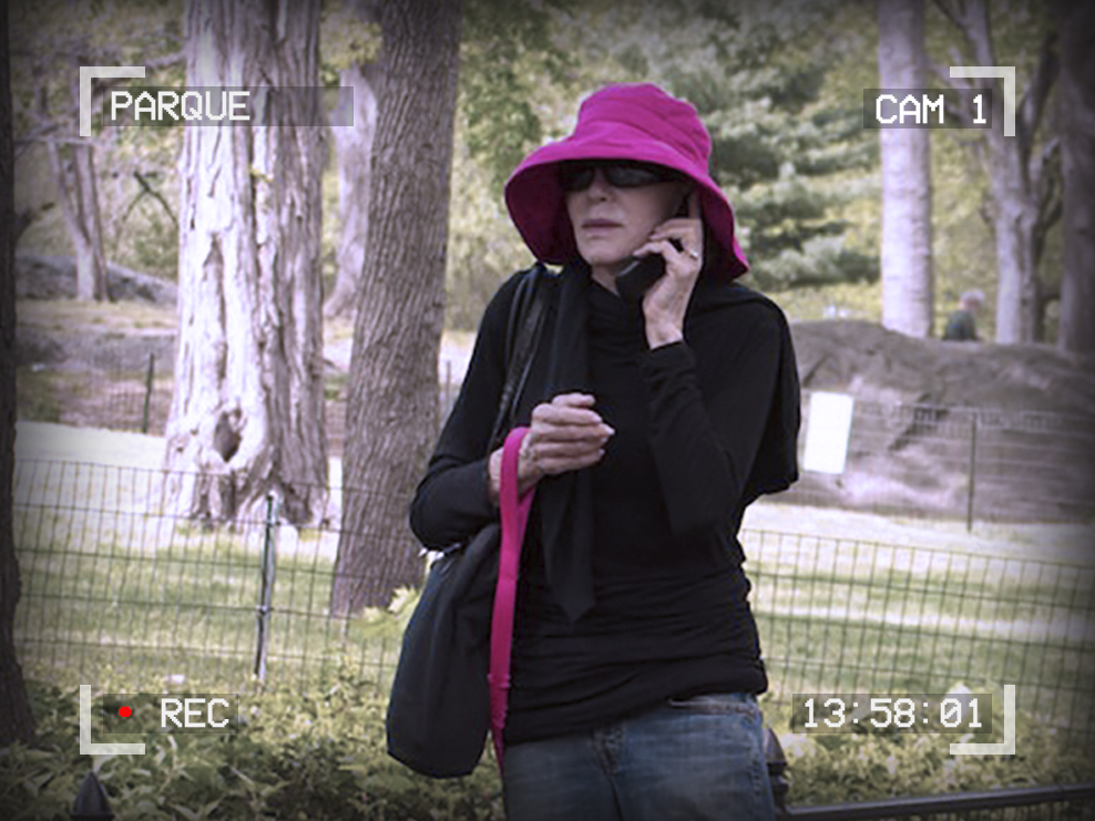 Photo of a woman talking on a cellphone. She is holding a leash in her hand. Text around the outside reads: Parque, Cam 1, 13:58:01, Recording