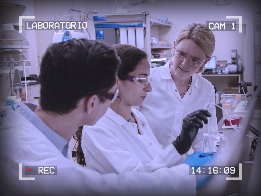 Photo of a professor helping students in a chemistry lab. Text around the outside reads: Laboratorio, Cam 1, 14:16:09, Recording