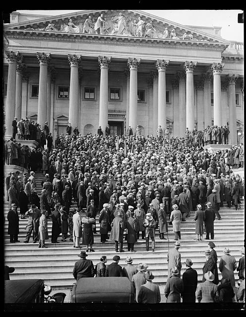 A veterans' interest group protests bonus bill delay. Protesting Congress' delay in considering the soldiers' cash bonus proposal, scores of Washington veterans paraded to the Capitol in a demonstration to seek immediate action. They were met on the Capitol steps by members of the House who are war veterans, where the photograph shows them being addressed by Rep. Patman of Texas. (Library of Congress Collection)