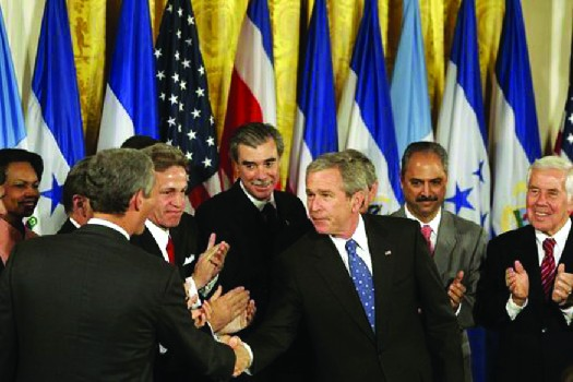 Domestic issues can sometimes become international ones when it comes to such topics as foreign trade. Here, President George W. Bush shakes hands with legislators and administration officials after signing the Central American Free Trade Agreement (CAFTA) Implementation Act on August 2, 2005.