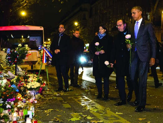 President Barack Obama, along with French president François Hollande and Paris mayor Anne Hidalgo, place roses on the makeshift memorial in front of the Bataclan concert hall, one of the sites targeted in the Paris terrorist attacks of November 13, 2015.