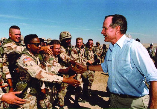President George H. W. Bush greets U.S. troops stationed in Saudi Arabia on Thanksgiving Day in 1990. The first troops were deployed there in August 1990, as part of Operation Desert Shield, which was intended to build U.S. military strength in the area in preparation for an eventual military operation.