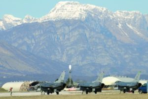 An image of several grounded fighter jets, with a mountain range in the background.