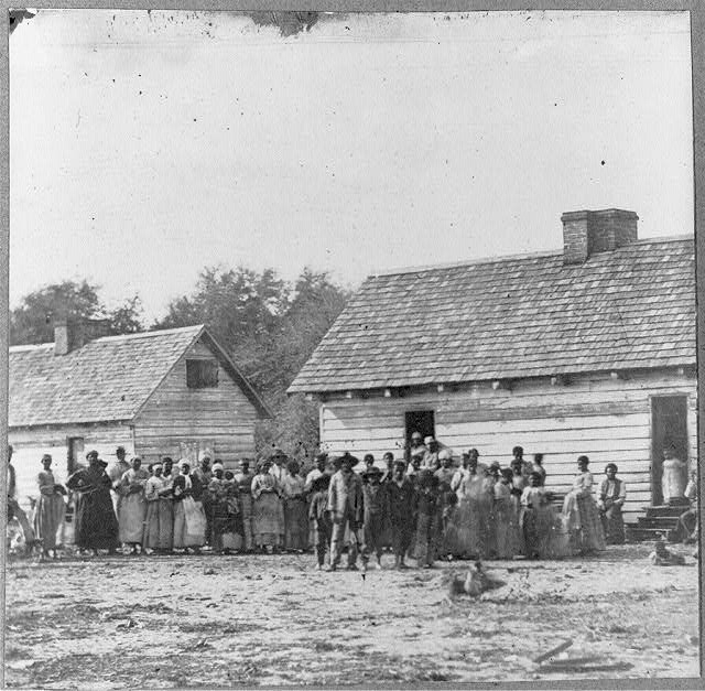 Photo of large group of slaves standing in front of buildings on Smith's Plantation in Beaufort, South Carolina.