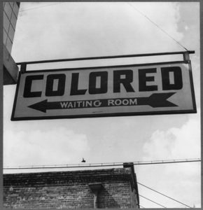 """Sign stating """"Colored Waiting Room"""" showing evidence of discrimination based upon race."""