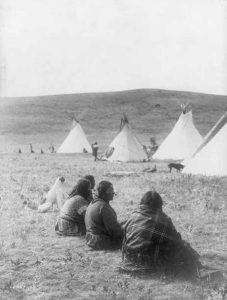 Title: Camp gossips--Atsina Creator(s): Curtis, Edward S., 1868-1952, photographer Date Created/Published: c1908 November 19. Medium: 1 photographic print. Summary: Four Atsina women and a dog, their backs to camera, sitting some distance from tipis and others. Reproduction Number: LC-USZ62-66670 (b&w film copy neg.) Rights Advisory: No known restrictions on publication. No renewal in Copyright office. Call Number: LOT 12322-A [item] [P&P] Repository: Library of Congress Prints and Photographs Division Washington, D.C. 20540 USA; Library of Congress at http://www.loc.gov/pictures/item/2002722343/.