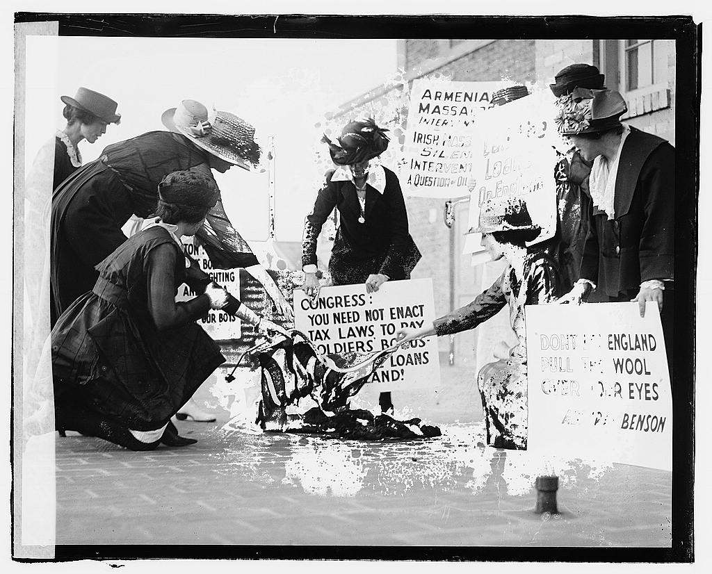A group of women carrying signs against America's support of the English against the Irish, burning a flag on the sidewalk, June 3, 1920; collection, Library of Congress at https://www.loc.gov/item/npc2007001720/