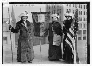 "Mrs. J. Hardy Stubbs, Miss Ida Craft, Miss Rosalie Jones; Photo shows 3 suffragettes with bag ""Votes for Women pilgrim leaflets."""