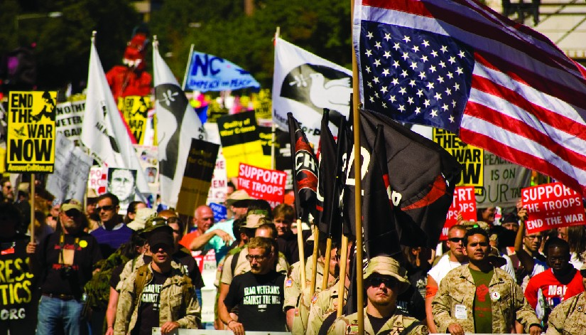 An image of a group of people, several of whom are holding flags and signs. One of the signs reads
