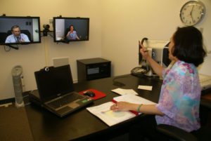 A man and a woman teleconferencing. The woman is sitting at a desk. There is a clock on the wall.