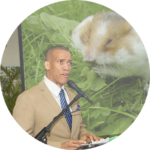 Round image (like an email avatar) of a man speaking. Projected behind him is a photo of a hamster