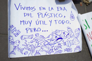 """Photo of a handwritten sign reading """"Vivimos en la era del plástico, muy útil y todo, pero..."""" with pictures of fish with x's for eyes, surrounded by plastic bottles"""
