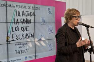 """Woman speaking into a microphone. The sign behind her reads """"La historia la ganan los que escriben"""""""