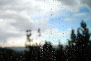 Photo of a blue sky through a rain-spattered window