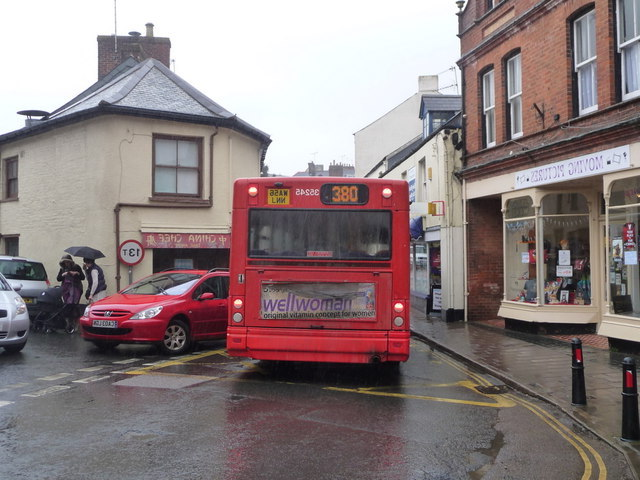 A bus to the right of a red car.