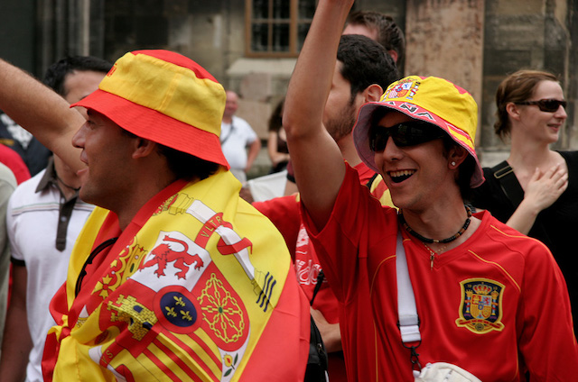 Two men wearing the colors of the Spanish soccer team.