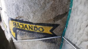 """sign pointing down stairs reads: """"bajando"""""""