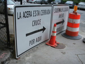 Sign and cones closing a sidewalk.