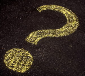 Question mark drawn in yellow chalk on black pavement