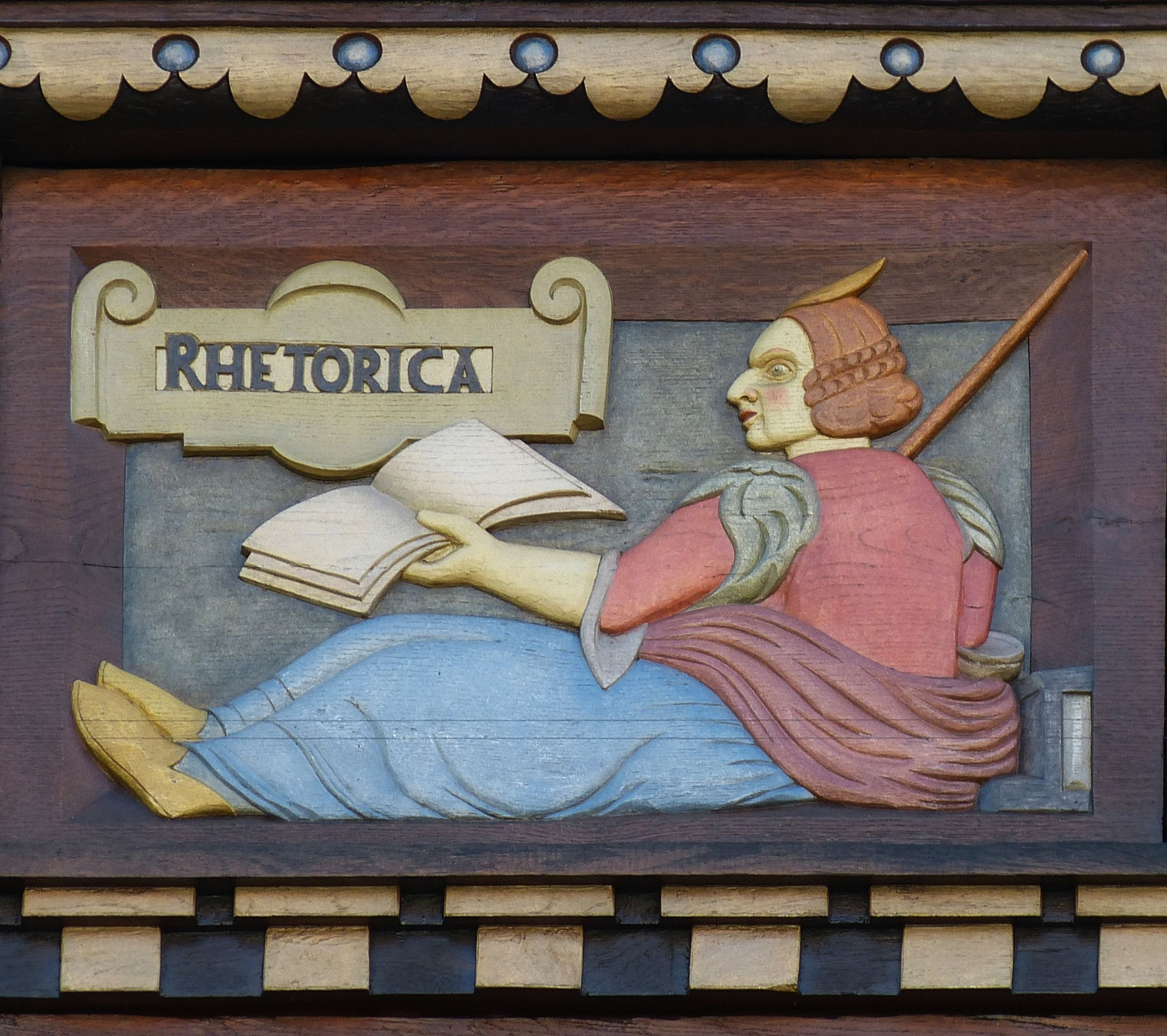 """wood carving showing a seated figure holding a book, labeled """"Rhetorica"""""""