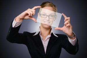 Businesswoman holding up translucent paper in front of her face