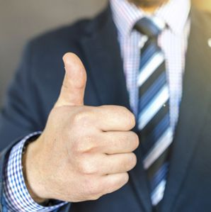 Man in suit giving thumbs up.