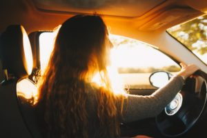 Photo shows a girl with long hair driving a car. The sun shines in through the window behind her.