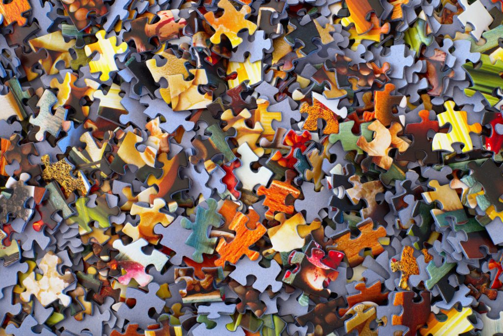 Close-up of a pile of puzzle pieces primarily in shades of yellow, orange, red, and green