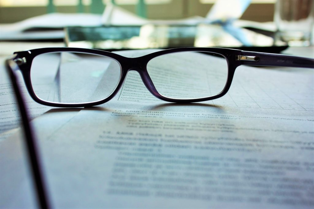 Dark-framed reading glasses laid down on top of a printed page
