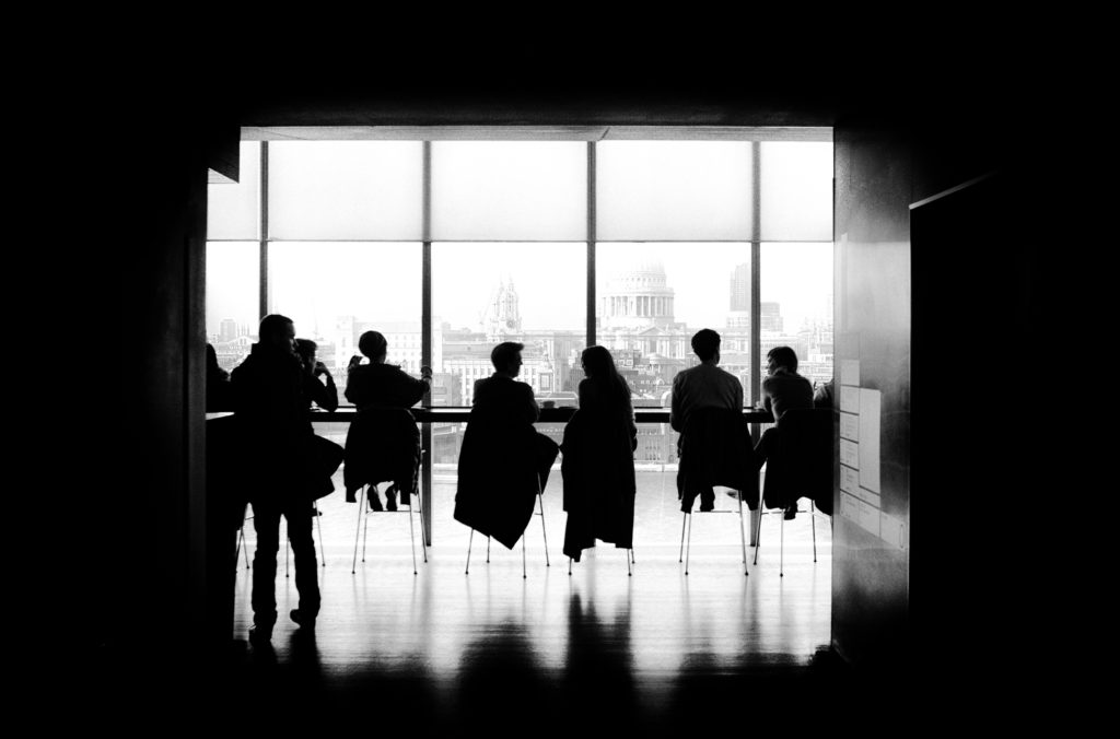 Black and white photo of several men and women sitting at a long, tall table in front of a large window; you can see a city skyline in the background outside.