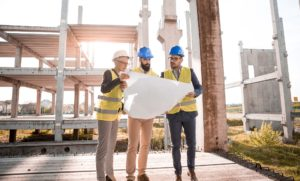 Three architects looking at a blueprint.