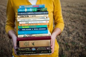 A woman holding a stack of different books.