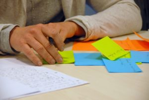 Someone writing on sticky notes and in a notebook.