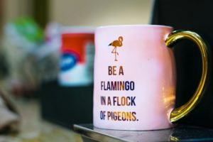 """A coffee mug featuring an icon of a flamingo and the quote """"Be a flamingo in a flock of pigeons."""""""