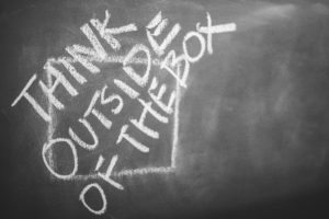 """The words """"Think outside of the box"""" written in white chalk."""