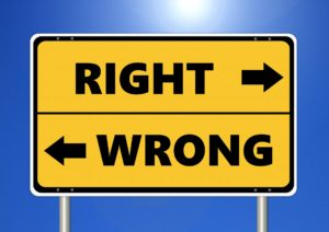 """A yellow road sign with two arrows pointed in opposite directions, next to one arrow is the word """"right"""" and next to the other arrow is the word """"wrong""""."""