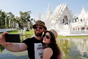 Two people taking a selfie in front of a white temple