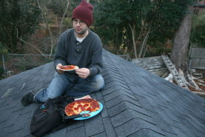 A man eating pepperoni pizza on the roof of a garage in Durham, North Carolina.