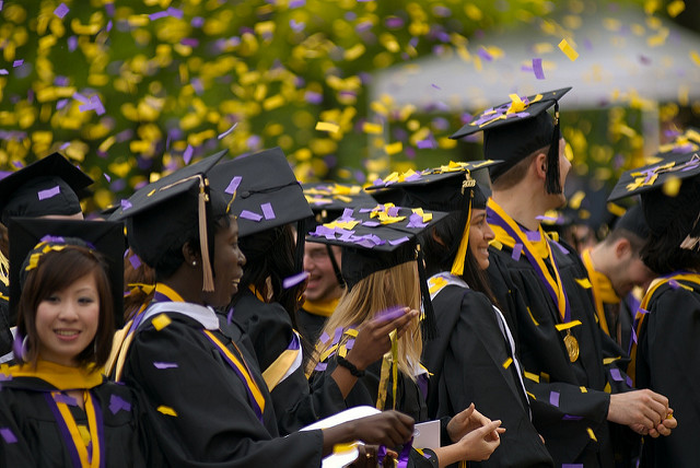 a group of college graduates in cap and gown.
