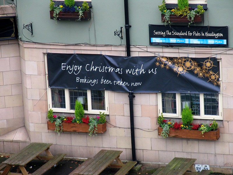"A small cafe with a banner that says,""Enjoy Christmas with us. Bookings been taken now."""
