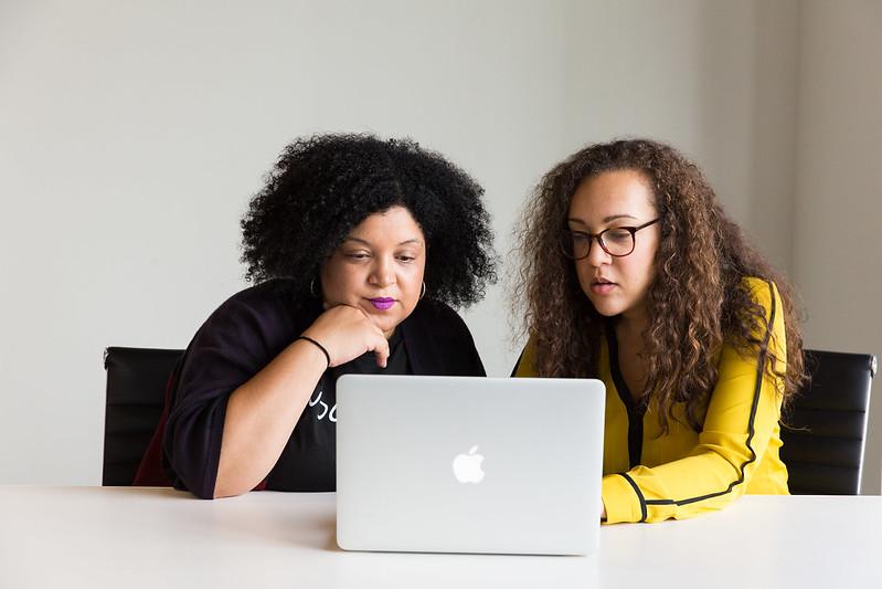 Two women reading a laptop screen