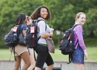 Two young women wearing backpacks walking outside among other students