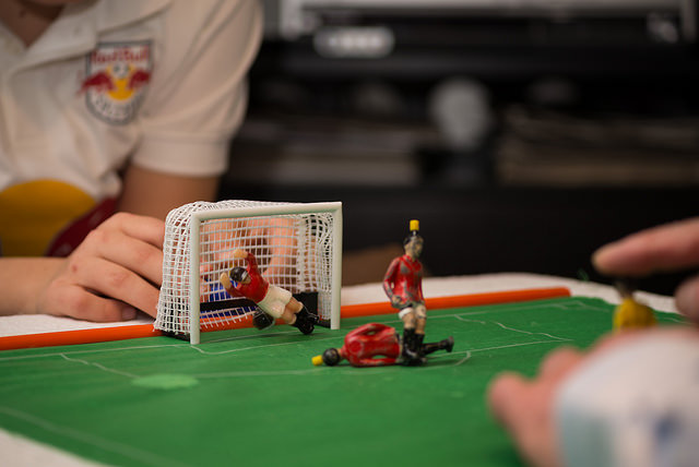 Close-up of two people playing with figurines on a miniature soccer field