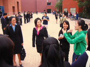group of young women, many in business suits, standing in a loose circle outdoors