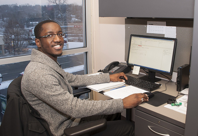 Young man sitting at computer in cubicle, smiling at camera