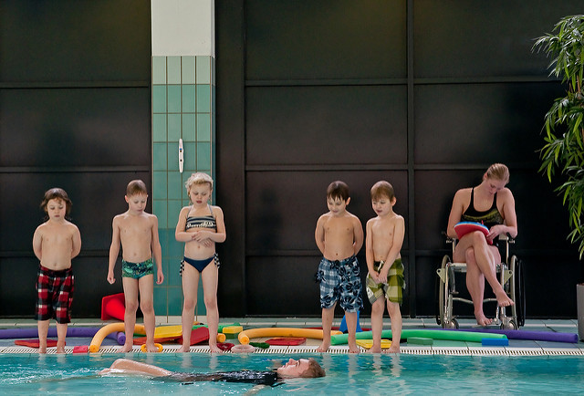 five children in swimsuits on the edge of a pool, watching an adult demonstrating a swim technique. A woman is seated with a paddleboard next to the children.